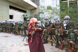 A child holds a toy gun alongside al-Shabaab fighters in Mogadishu stadium